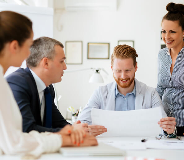 Group of four business agents going over paperwork in a meeting room